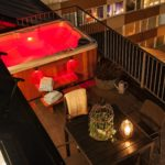 Overhead view showing serenity 4000 hot tub with red light within the tub. The tub is next to an outdoor dining area.