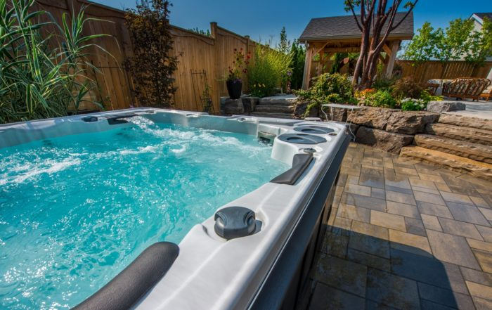 An 8-person hot tub with water in it displaying the water fall pillow, interlock patio with natural landscaping and outdoor eating area