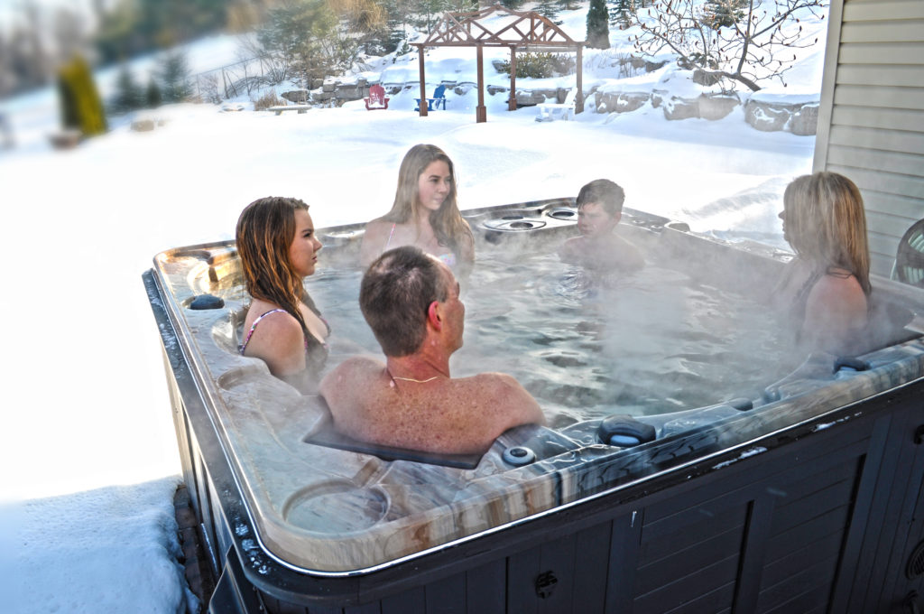 The tub features enough space for a family of 6 people with a winter backdrop