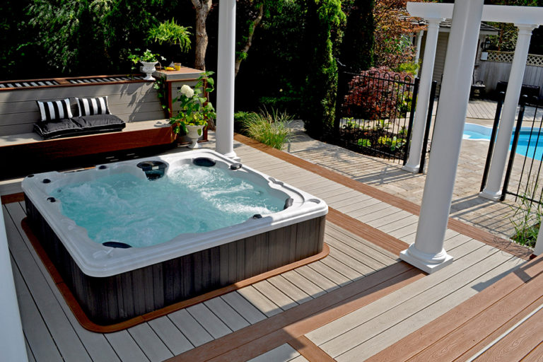 An award winning photo of a beautifully landscaped back yard with a serenity hot tub lowered into a custom deck with a pool in the background.